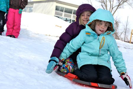 Two YG'ers sledding down a hill.